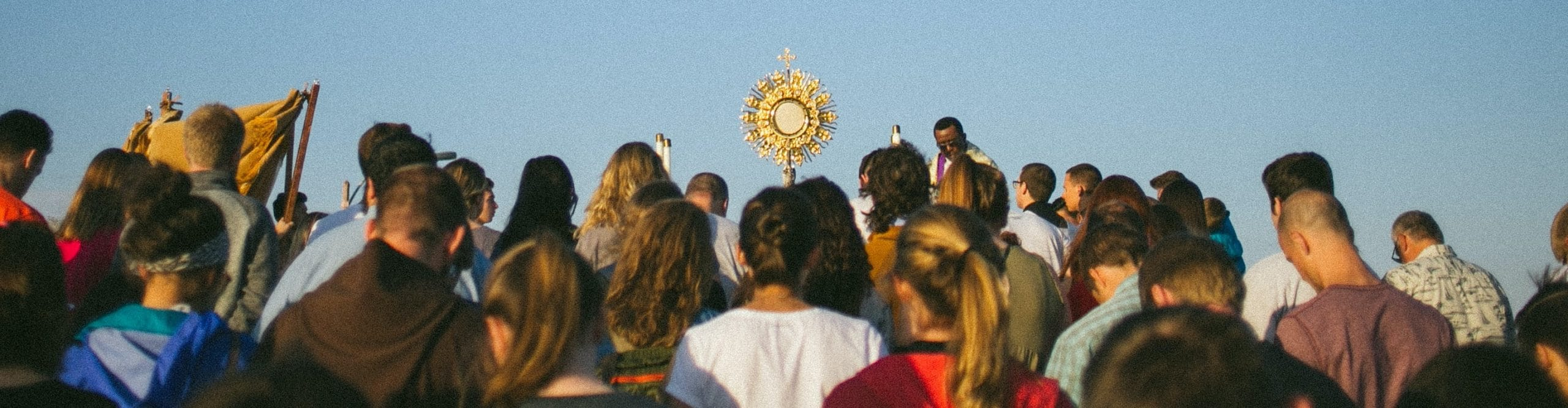 A group of Catholic pilgrims gather for the Eucharist with monstrance held high.