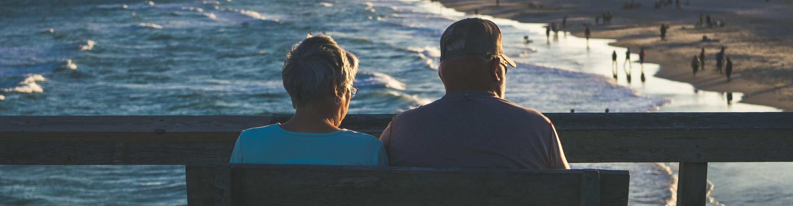 Retired pilgrims sit on a bench and at looks out at the ocean and beach.