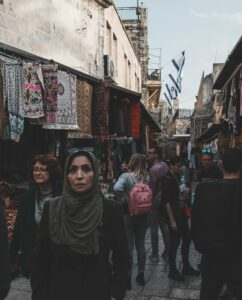 People of many cultures walk through Jerusalem with flags of Israel in the background